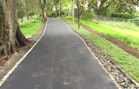 """Urban Solutions worked with the client to come up with an innovative solution to protecting tree roots by providing an attractive and flexible asphalt pavement with basalt-filled drainage channel. This solution avoided an expensive and ugly concrete """"bridging"""" alternative."""